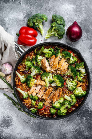 Asian egg noodles with vegetables and meat on cooking pan. Gray background. Top view.