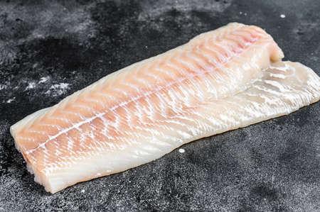Raw Norwegian skrei cod fish fillet. Black background. Top view.