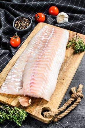 Fresh Raw Cod loin fillet with thyme. Black background. Top view. Zdjęcie Seryjne