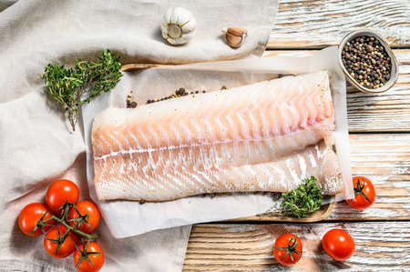 Fresh Raw Cod loin fillet with thyme. White wooden background. Top view. Zdjęcie Seryjne