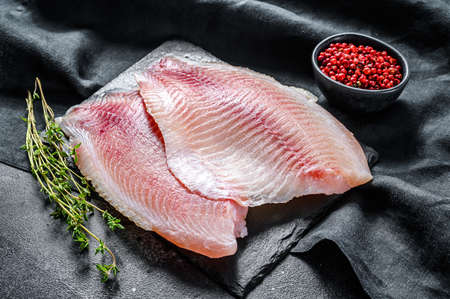 Raw telapia fillet on a chopping Board with thyme and pink pepper. Black background. Top view. Zdjęcie Seryjne