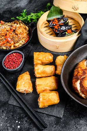 Chinese cuisine dishes set, food black background. Chinese noodles, dumplings, peking duck, dim sum, spring rolls. Famous. Top view.