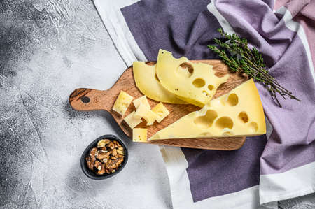 Maasdam cheese with walnut and thyme. White background. Top view.