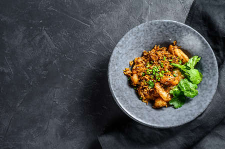 Fried rice with shrimp prepared in wok. Black background. Top view. Copy space.
