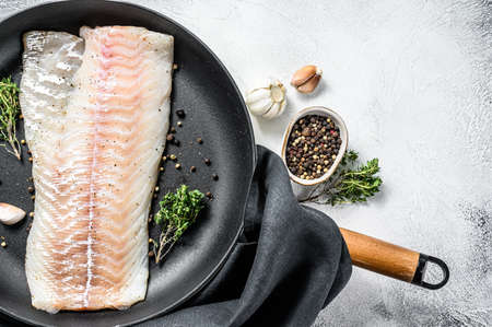 Raw cod loin with herbs in a frying pan. Gray background. Top view. Copy space. Zdjęcie Seryjne