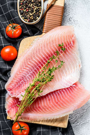Telapia fillet on a cutting Board with thyme and pink pepper. White background. Top view.