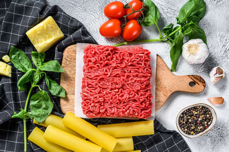 Ingredients for cooking cannelloni pasta with ground beef. Italian cuisine. Gray background. top view.