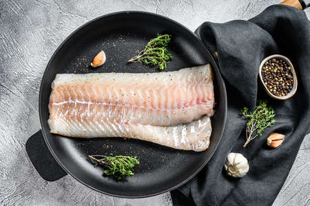 Raw cod fillet with thyme and herbs in a pan. Cooking fresh fish. Gray background. Top view.