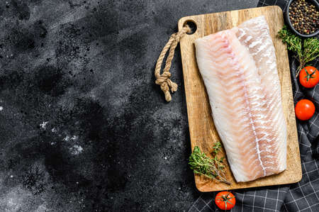 Raw cod fillet with and herbs on rustic wooden cutting board. Black background. Top view. Copy space.