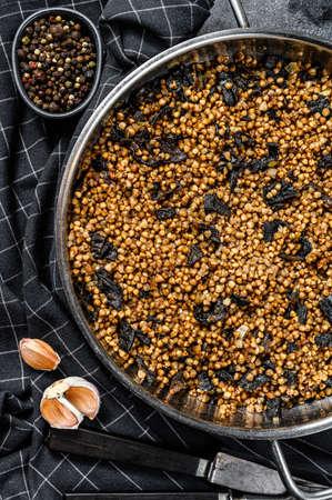 Buckwheat porridge with mushrooms. Vegan food. Russian, Ukranian cuisine. Black background. Top view. Copy space. Zdjęcie Seryjne