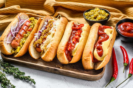 Hot dogs fully loaded with assorted toppings on a tray. Delicious hot-dogs with pork and beef sausages. White background. Top view.