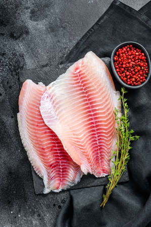 Fresh telapia fillet on a chopping Board with thyme. Black background. Top view. Zdjęcie Seryjne