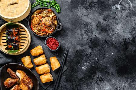 Chinese food. Noodles, dumplings, stir fry chicken, dim sum, spring rolls. Chinese cuisine set. Black background. Top view. Copy space.