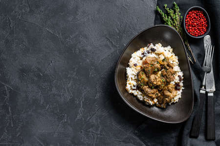 Traditional Indian curry lamb meat masala. Black background. Top view. Copy space.