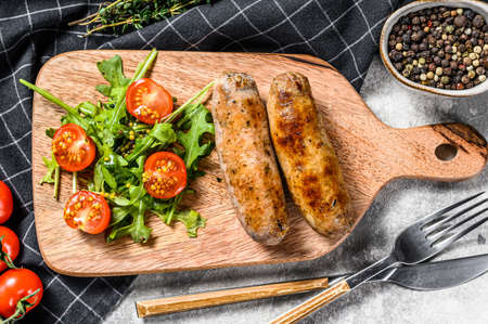 BBQ Grilled sausages on a chopping Board with tomato and arugula. Gray background. Top view.