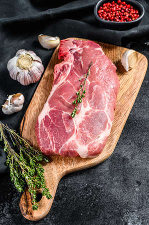 Raw marble pork steak on a wooden chopping Board. Organic meat. Black background. Top view. Stok Fotoğraf