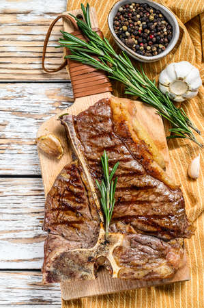 Grilled Porterhouse steak on a chopping Board. Cooked beef meat. White wooden background. Top view. Stok Fotoğraf