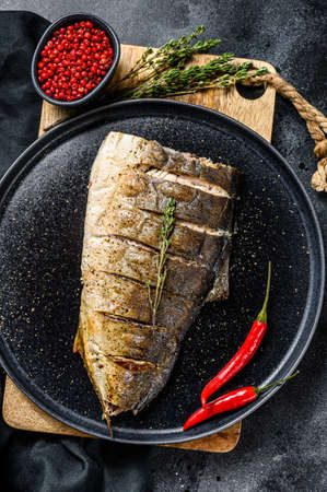 Grilled Yellowtail, Japanese amberjack fillet on a plate. Black background. Top view.