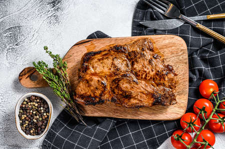 Roast pork steak on a chopping Board. Organic meat. Gray background. Top view.