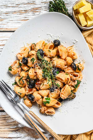 Pasta puttanesca with tuna fish, tomatoes, garlic and black olives. White background. Top view