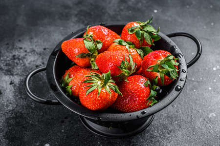 Fresh red strawberries in a colander. Black background. Top view.