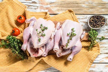 Whole raw Free range chicken with thyme and spices. White background. Top view. Stockfoto