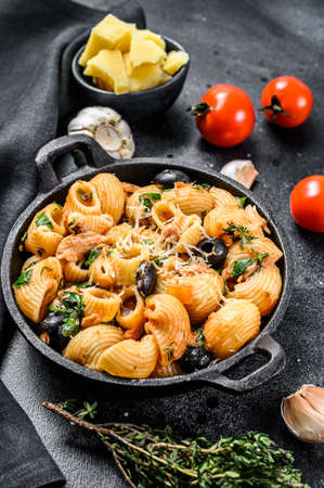 Traditional italian pasta with tomato, olives, capers, anchovies. Conchiglie rigate, puttanesca. Black background. Top view. 免版税图像