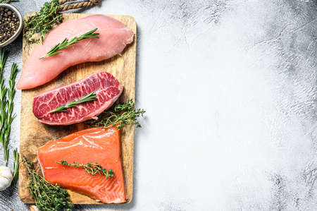 Three types of steaks. Beef top blade, salmon fillet and Turkey breast. Organic fish, poultry and beef meat. Gray background. Top view. Copy space. Stock fotó