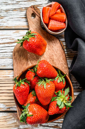 Strawberries in a wooden bowl on a chopping Board. White background. Top view. 免版税图像