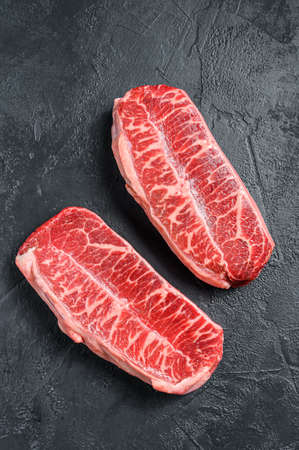 Raw top blade steak dry-aged. Black background. Top view. Banco de Imagens