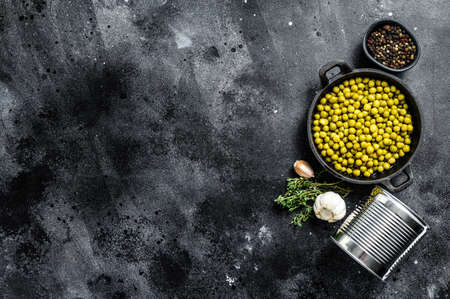 Canned green peas in a frying pan. Canned food. Black background. Top view. Copy space.