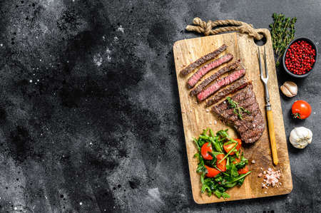 Grilled sliced Denver steak on a cutting board. BBQ beef. Black background. Top view. Copy space. Imagens