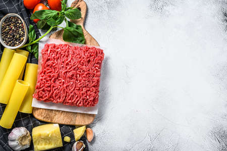 Ingredients for cooking cannelloni pasta with ground beef. Italian cuisine. Gray background. top view. Copy space.