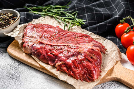Flat iron steak, raw meat, marbled beef . Gray background. Top view. Stock Photo