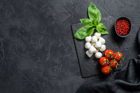Mini mozzarella cheese, Basil leaves and cherry tomatoes, cooking Caprese salad. black background. top view. Copy space. Stockfoto