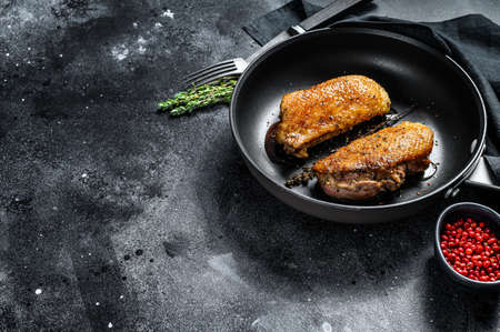 Grilled duck Breasts in a pan. Black background. Top view. Copy space.
