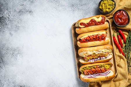 Hot dogs with assorted toppings. Delicious hot-dogs with pork and beef sausages. White background. Top view. Copy space. Standard-Bild