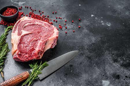 Ribeye on the bone or cowboy steak. Raw Marble beef. Black background. Top view. Copy space.