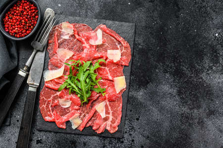 Italian Beef carpaccio with arugula salad, parmesan cheese. Black background. Top view. Copy space. Stock Photo