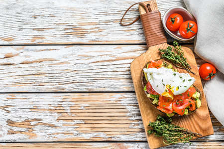 Salmon and Poached egg on grilled toast. White wooden background. Top view. Copy space.