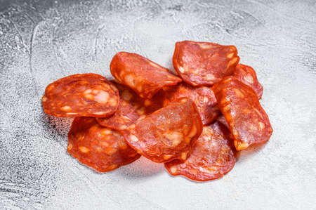 Chorizo sausage thin cut. Spanish salami with spices, paprika, pepper. Spicy food. White background. Top view.