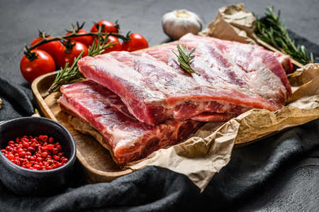 raw pork meat ribs with ingredients for cooking rosemary and garlic in a wooden bowl. Black background. Top view.