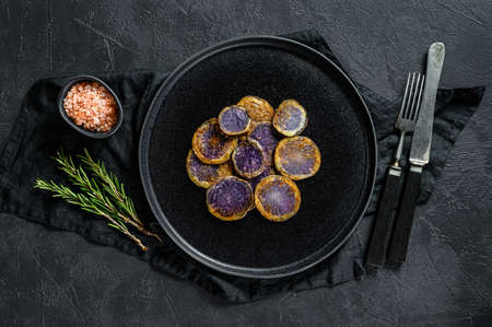 Baked purple potatoes with rosemary. Black background. Top view. Space for text.