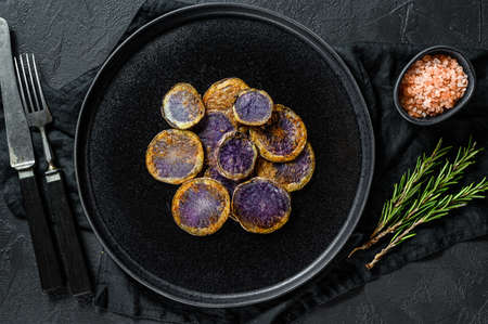 Fried purple potatoes with rosemary. Black background. Top view. Space for text. Banque d'images