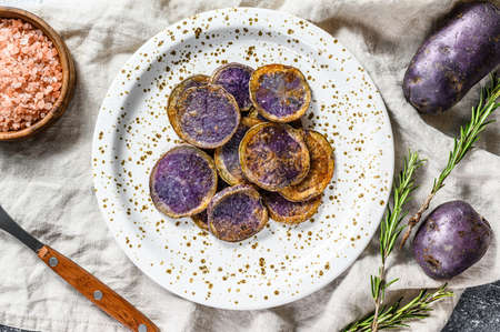 Baked purple potatoes with pink salt. Gray background. Top view. Banque d'images