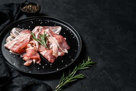 Pork bacon on a black plate. Farm organic meat. Black background. Top view. Space for text.