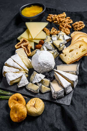 Assortment of French cheese with honey, nuts and figs on cutting board. Black background. Top view.