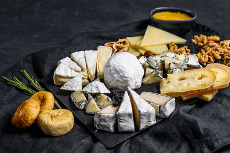 Assortment of French cheese with honey, nuts and figs on cutting board. Italian antipasto. Black background. Top view. 写真素材