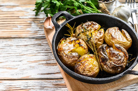 Jacket baked potato with garlic and rosemary in a pan. White background. Top view. Copy space.