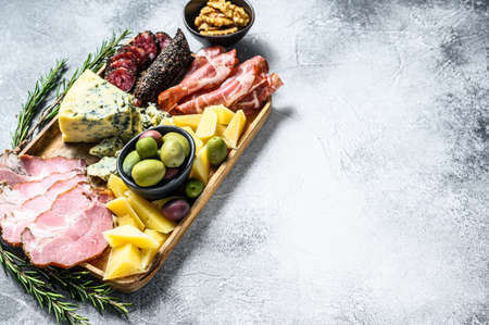 Antipasto platter with ham, prosciutto, salami, blue cheese, mozzarella and olives. Gray background. Top view. Space for text.